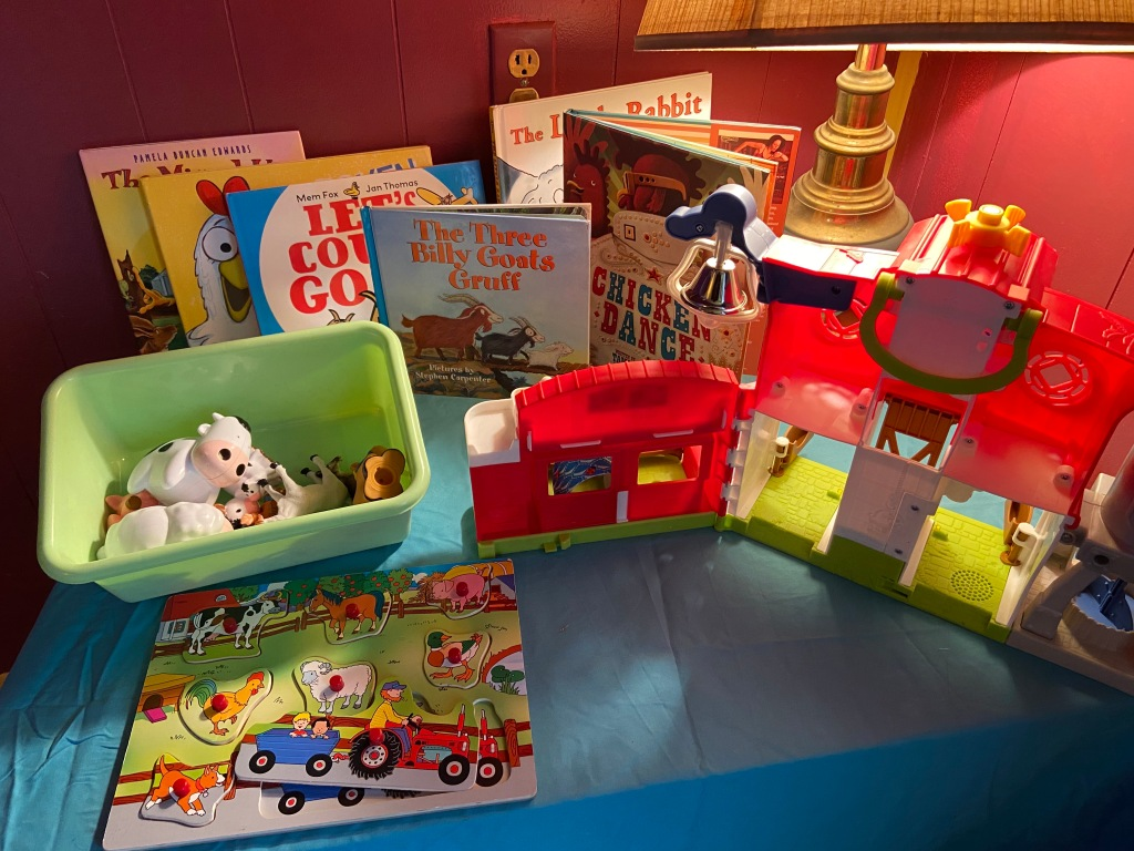 a farm themed play station, featuring related books, puzzles, and figurines.