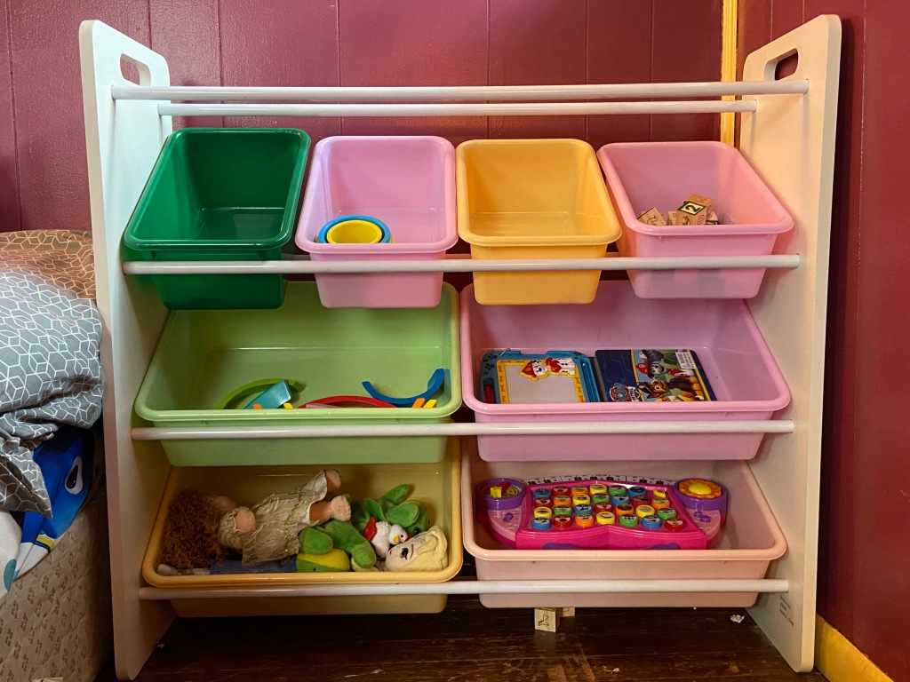 This image shows a child's toy storage. Colored bins house play items in a visible, reachable way that is easy to organize and change over time.
