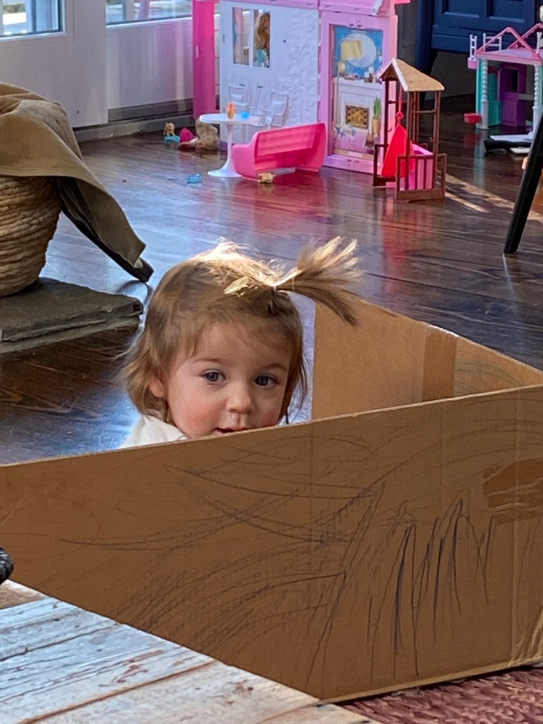 Baby peaks her head out of a box decorated with crayon markings to investigate the world beyond her small fort..